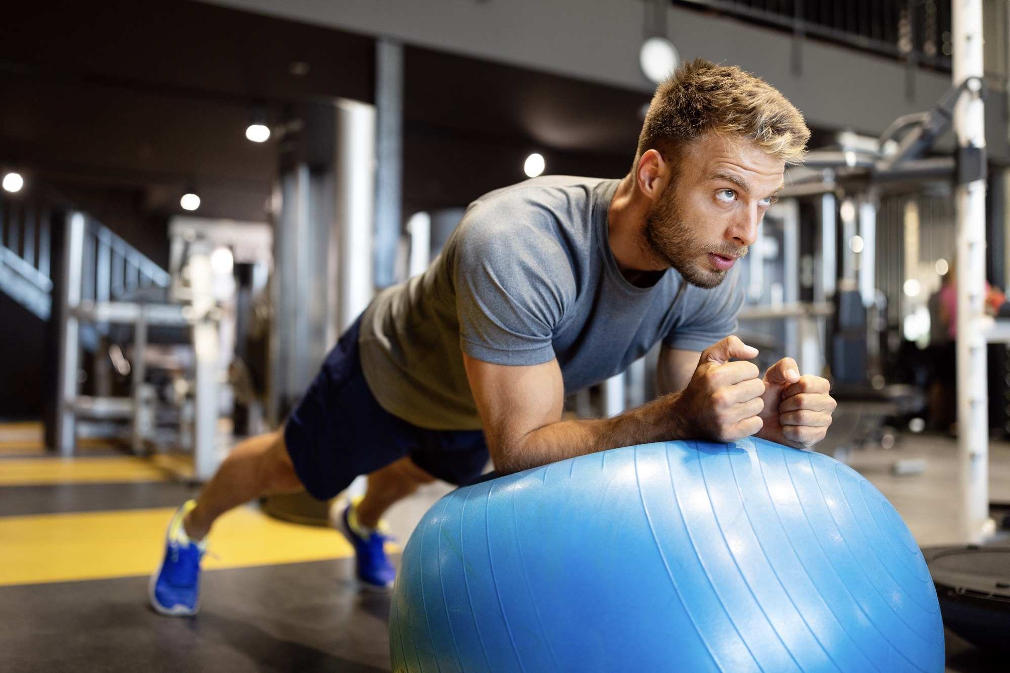 Fit man doing fitness exercise on pilates ball in gym