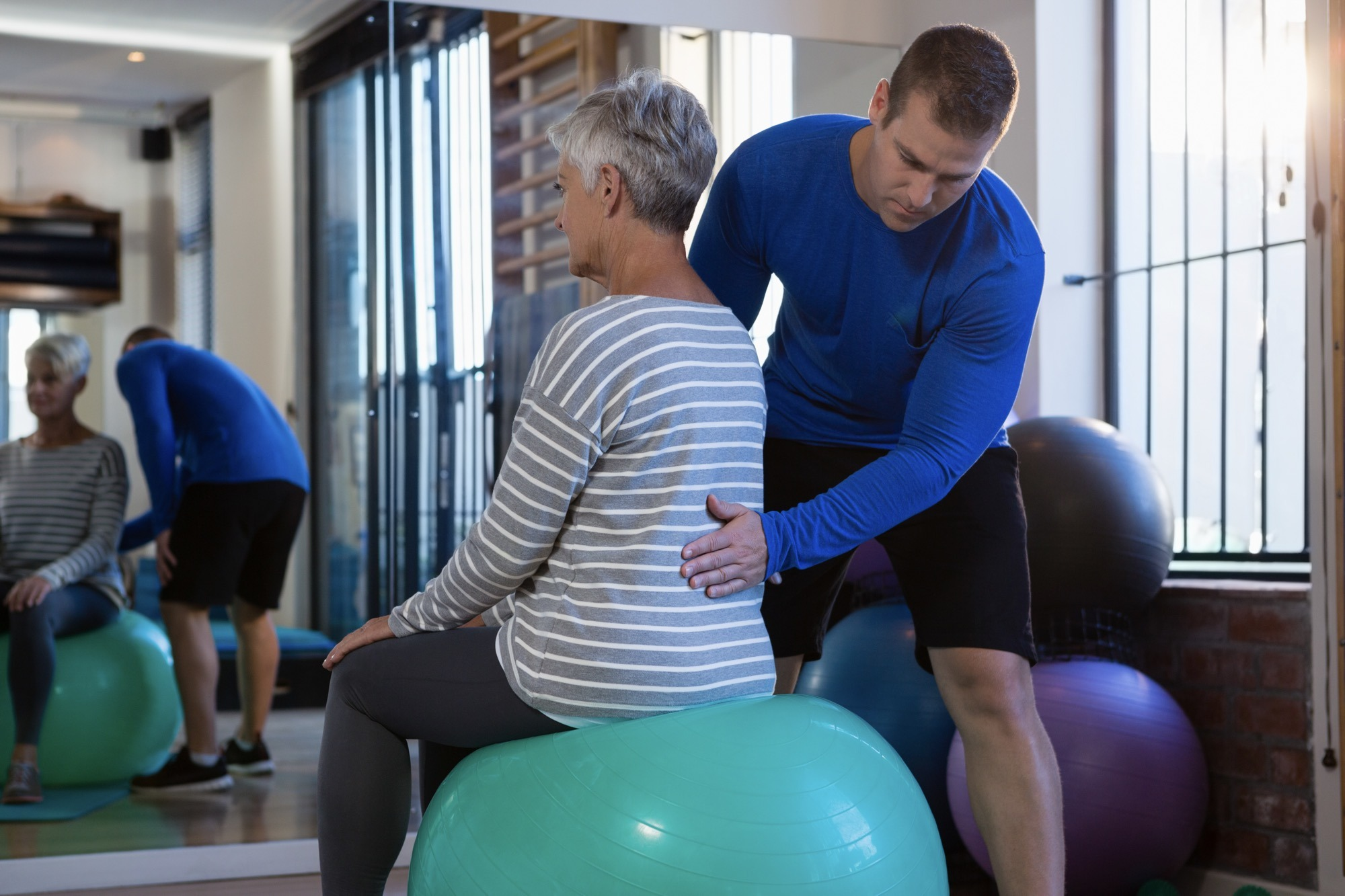 Physiotherapist assisting senior woman on exercise ball